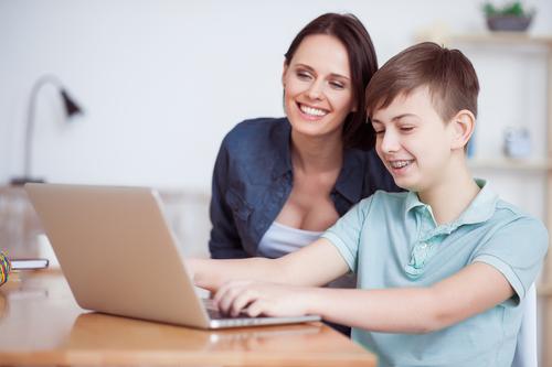 Moeder met zoon bezig met de laptop en social media